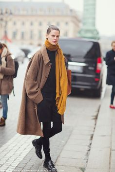 Saskia de Brauw in a brown wool coat and mustard yellow scarf.