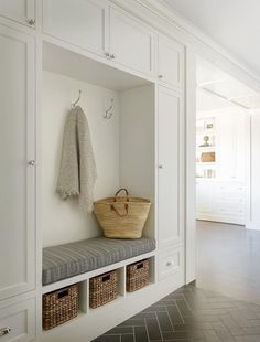 Beautiful white and gray mudroom with gray herringbone tile floors boasts built…