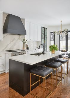 Three Nuevo Chi Stools are placed at a black shaker island donning a white quart. Three Nuevo Chi Stools are placed at a black shaker island donning a white quartz countertop and fitted with a stainless steel sink and a matte black gooseneck faucet. Black Kitchen Island, Black Kitchen Faucets, Stools For Kitchen Island, Kitchen Island Quartz, Black Quartz Kitchen Countertops, Faucet Kitchen, White Counters, White Cabinets, Home Decor Kitchen