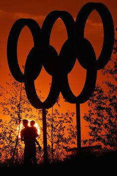 A man and boy have their photograph taken as the sun sets behind the Olympic rings