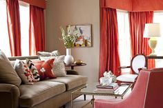 These colors together are beatutiful!  The red-orange curtains make this room.  I like how the beige walls and couch are decorated with warm-colored pillows, and curtains.  This accented neutral room is one of my favorites.