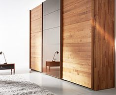 Luxurious modern sliding door wardrobes shown in solid beech heart wood and coloured glass