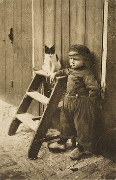 Een kleine jongen in dracht met een kat bij een trapje tegen een houten gevel van een woning. 1905-1920 #NoordHolland #Volendam