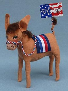 """Annalee 7"""" Patriotic Donkey with VOTE Sign - Mint - Prototype Annalee Doll Description: Last one. Open eyes, tan body, red, white and blue saddle and reins, holds American flag """"VOTE"""" sign. Great gift for any Democrat, Donkey or Mule colector. Never put into production - one of a kind! Companion is 112603."""