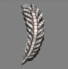 A late 18th/early 19th century diamond feather brooch  Realistically modelled as a curved feather, set throughout with cushion-cut diamonds within closed back settings, mounted in silver and gold, later pin fitting, diamonds approx. 4.80ct. total, length 5.8cm.