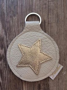 Schlüsselanhänger aus crèmefarbenem Rindsnappaleder mit einem goldenen applizierten Stern. Der Durchmesser des Anhängers beträgt 7,5 cm. Inklusive des Ringes hat er eine Länge von 10,5cm.