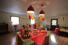 The key to using inexpensive materials is to use A LOT of them and work the scheme. This room already had red retro details, so we picked a theme to take advantage of that.  #red #yellow #babyshower #decor #retro #vintage
