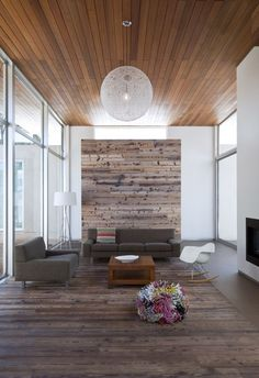 Modern living space with wood-paneled ceiling and reclaimed wood on the floor and accent wall