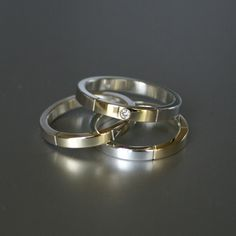 zilveren ringen waarin gedeeld goud uit trouwringen is verwerkt en een diamant is toegevoegd.