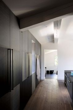 Spare dressing area, clean lines, slab  doors with alternating grain direction, vintage wood floors