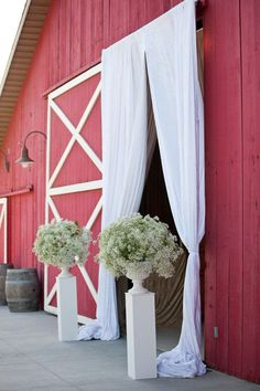 Red barn doors decorated with white curtains and flowers #weddingdecor #farmhouse #rustic #barn #farmhousewedding
