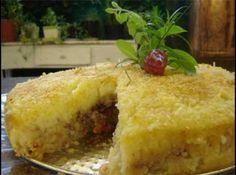 Receita de Torta de batata e carne moída - Purê:, 2 batatas grandes cozidas e espremidas (550 g), 1 ½ de xícara (chá) de leite desnatado (300 ml), 1 xícara (chá) de Aveia em Flocos Regulares Quaker (80 g), sal a gosto, pimenta do reino moída na hora, ¼ de xícara (chá) de queijo parmesão ralado para decoração (18 g), Recheio:, 1 ½ colher (sopa) de azeite (15 g), 1 cebola picada (100 g), 350 g de carne moída magra, ½ xícara (chá) de castanha-do-pará picada (75 g), ¼ xícara de azeitonas pretas…