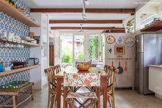 Sala de jantar tem parede revestida com ladrilho hidráulico com padronagem geométrica e prateleiras de madeira.