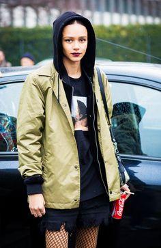 Binx Walton wears a green parka, black hoodie, black graphic tee, distressed skirt, and fishnet tights