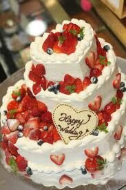 Heart shaped wedding cake topped with various berries