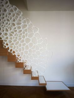 Architect Ammar Eloueini worked with architect Marc Fornes of THEVERYMANY™ to complete this Corian screen/handrial that spans the side of this wooden block staircase in Paris.