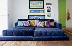 """Na escolha dos móveis, a arquiteta Letícia Arcangeli sabia o que queria: um sofá enorme, bom para se esparramar. De tipo chaise, ele foi difícil de encontrar, mas valeu o esforço. """"Eu chego em casa à noite e vejo televisão deitada nele"""", diz"""