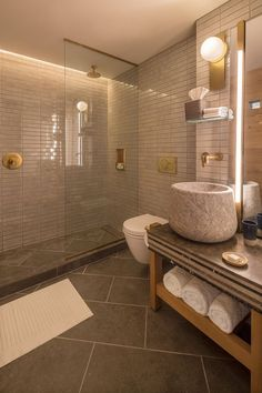 In this modern hotel bathroom, tiles cover the walls while in the shower, hidden lighting creates a soft glow. #ModernBathroom #BathroomDesign
