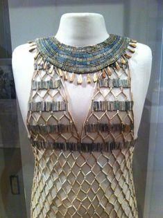 Detail, bead-net dress and broad collar whose remains werefound during excavations ofthe tomb of a female interred at Gizaduring the reign of King Khufu, ca. 2500 BCE.Both pieces were reconstructed by Millicent Jick (1928-2010), a volunteer gallery instructor at the Museum of Fine Arts, Boston. The cylinder and diskbeads are Egyptian faience. The pendants on the broad collar are made of gold.Image courtesy Museum of Fine Arts, Boston.