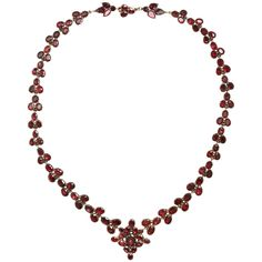 Behold the Treasure of a Brilliant Georgian Garnet Necklace. The color of these garnets is so lustrous that it has to be seen to be appreciated. Elongated poesies extend from a central flower like medallion to form a graceful v shape at the neck. The garnets are set in 15kt gold as is most Georgian garnet jewelry but this is no ordinary example. This is a treasure. The condition is perfect. English in origin. c. 1820