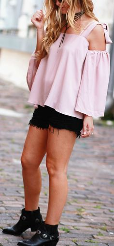 Bohemian fall transition outfit styled with a blush off the shoulder top, black distressed jean shorts, and Dolce Vita concho booties
