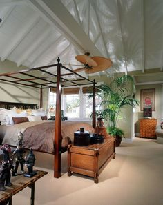A white-painted wood-paneled vaulted ceiling with high rafter reflects the shadow figures of the palm plant below and creates a dreamy island-feel effect.