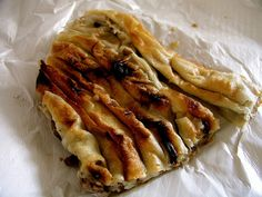 Burek (Bosnia & Hercegovina). 'Filo pastry is filled with aromatic minced (ground) meat – or spinach (zeljanica) – and onion, cheese and herbs (sirnici), then rolled, glossed with either butter or olive oil and baked till golden. Burek can be eaten at any hour: for breakfast accompanied by black tea, or after a busy night in the bars of Sarajevo's Baščaršija district.' http://www.lonelyplanet.com/bosnia-and-hercegovina