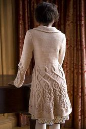 """Designer Notes: """"To add swing to the skirt, I added a side gore that tapered from the hem to the waist at each side. Doing so added at least 12 inches (30.5 cm) to the bottom circumference of the skirt, allowed the edges to meet gracefully at the center front, and added centered cable motifs along each side of the coat."""" --Michele Rose Orne"""