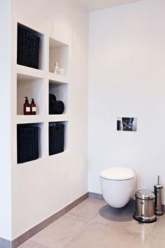 Ved toilettet har Alexandra Høholt valgt indbyggede hylder. En æstetisk måde at få plads til parfumer og cremer. Toiletspand og børste er fra danske Vipp.