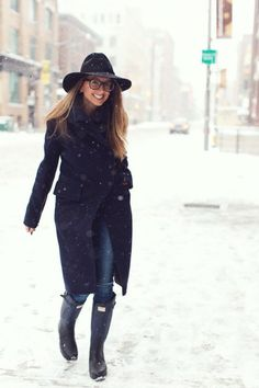 Street Style: bundled-up looks from the industry crew at The ShOws Weather-appropriate Hunter rain boots dress down the sophisticated floppy hat and fitted coat