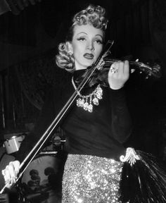 """Marlene Dietrich plays her violin on the set of """"Seven Sinners"""""""