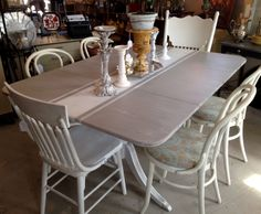Paint treatment on a 40's Duncan Phyfe drop leaf dining table, gray chalk paint with stripe makes a very Frenchy look. Adding mismatched white chairs completes the look,