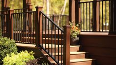 Trex Reveal Aluminum Railing in Charcoal Black with Transcend Treehouse Posts and Transcend Tiki Torch and Lava Rock Decking