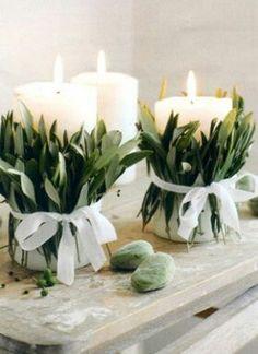 Centros de mesa con hojas y cintas envolviendo velones
