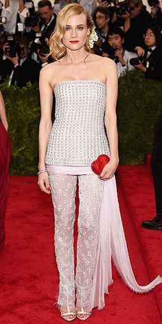 The Most Jaw-Dropping Dresses at the 2015 Met Gala | DIANE KRUGER | in a silver bustier top with sheer pants (both Chanel Haute Couture), plus fine jewelry by the line – and accessorized with a Judith Leiber clutch, T-strap heels and fresh flowers in her hair.