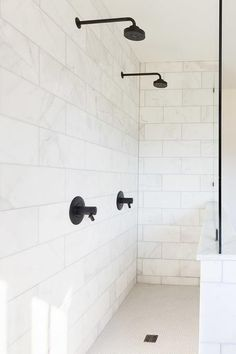 Stunning long shower clad in honed white marble wall tiles boasts side by side oil rubbed bronze shower heads positioned over white hexagon floor tiles.