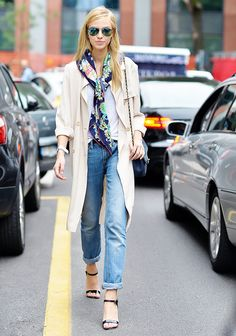 A white t-shirt is paired with a silk scarf, trench, cuffed jeans, and strappy sandals
