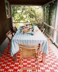 Dining Room - A red geometric rug beneath a dining table and chairs on a screened-in porch