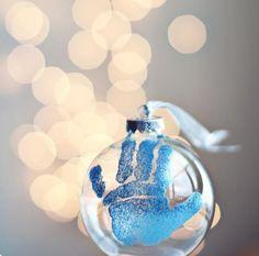 une boule en verre de Noël décorée d'une main bleue de bébé
