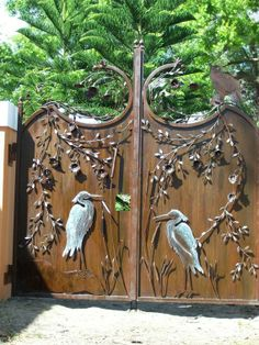 Two-panel, solid wrought iron privacy gate with egrets. Natural iron color with leaves and flowers on both sides.