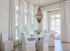 An Arteriors Maxim Chandelier hangs over an oval marble top dining table is seating off-white slipper dining chairs in front of windows.