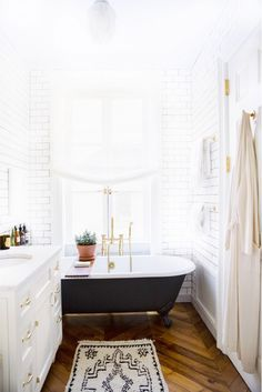 Black painted clawfoot tub with brass hardware and herringbone floors.
