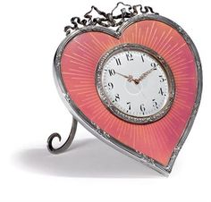 A Fabergé Silver-Gilt and Guilloché Enamel Desk Clock, workmaster Michael Perchin, St Petersburg, 1899-1903. Heart-shaped, enameled in translucent pink over a sunburst guilloché ground, centring a white enamel dial within a ribbon-tied laurel bezel, all within a ribbon-tied and leaf-clad reeded border, surmounted by a tied ribbon crest.