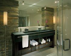 bathroom double sink granite countertops stone columns wall standing lamps sconces bathroom tiles floor glass door shower rectangular mirror door less cabinets of Aesthetically Pleasing Trough Bathroom Sink with Two Faucets