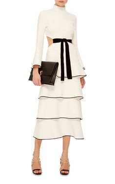 This dress by **Proenza Schouler** features four tiers with black edging, bell sleeves and black tie at the waist.