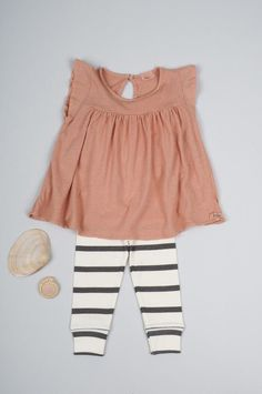 Layout of black & white striped leggings with blush pink blouse
