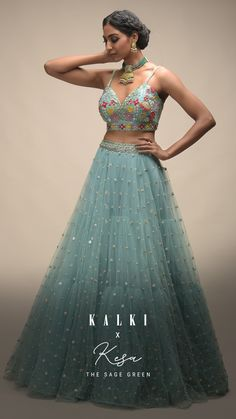 Adorned with resham, cut dana, zardozi and pearls embroidered in spring blooms, the sage green lehenga specializes in the fluffy tulle scattered with sequins as a unique element. With blooming florals and embroideries, the pastel lehenga is teamed with a sweetheart cut out bustier with spaghetti straps. The understated flair and the hand-beautified sheer dupatta just looks on point and can be a really offbeat one to try for your sangeet. What say, brides? Indian Fashion Dresses, Muslim Fashion, Fashion Outfits, Lehenga Crop Top, Wedding Outfits, Wedding Dresses, Lehenga Saree Design, Green Lehenga, Half Saree Designs
