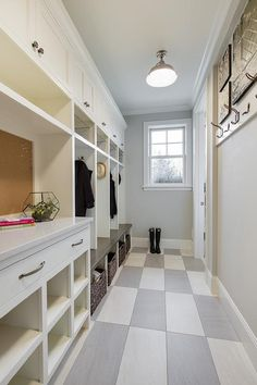 Long and narrow mudroom features a wall of built-in cabinets, open lockers and a bench next to a message center with cork board alongside white and gray checkered tiled floors.