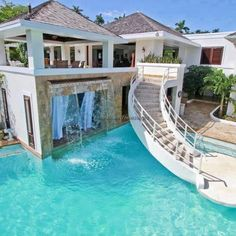 Gorgeous pool home with spiral stairs leading to living space and water fall ledge.