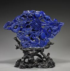 """Large Chinese Carved Lapis Lazuli Group Unusually large and fully openwork carved, Chinese lapis lazuli group; depicting two writhing dragons and a phoenix around a large lotus blossom (possibly color enhanced); L: 17 1/2"""", root wood stand"""